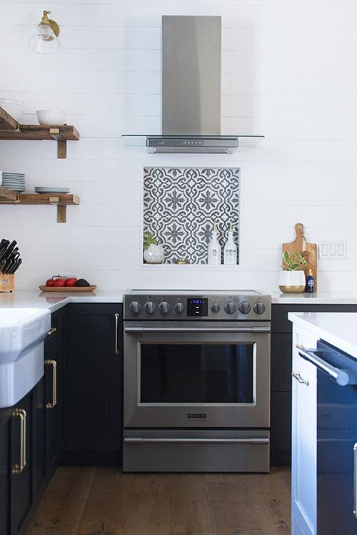 farmhouse kitchen, frigidgaire professional range, range hood, cement tile, open shelving, navy blue cabinets, farmhouse sink, brass wall sconce