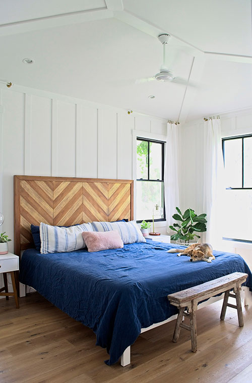 farmhouse bedroom, chevron headboard, board and batten, navy blue duvet cover, antique chinese bench, fiddle leaf fig