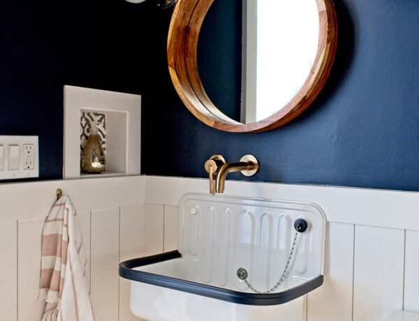 blue and white farmhouse powder bathroom with shiplap walls bucket sink navy blue walls round wood mirror black door wood floor