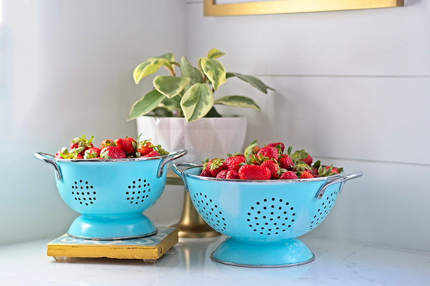 bright blue colanders full of strawberries on a kitchen counter