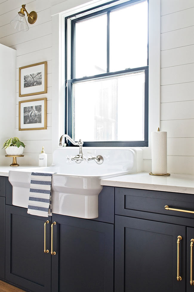 modern farmhouse cottage kitchen with navy blue cabinets with satin brass hardware and apron farmhouse sink in front of window