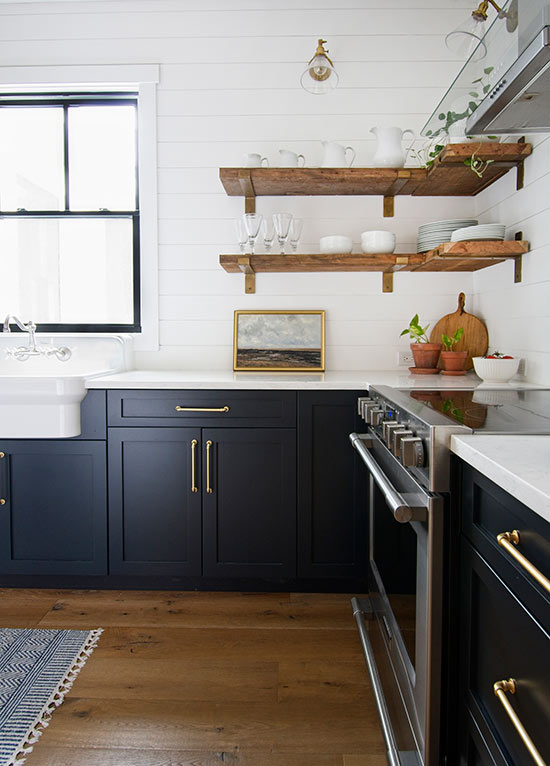 modern farmhouse kitchen with dark navy blue cabinets with gold brass hardware and open shelving with shiplap backsplash and farmhouse apron sink in front of black window