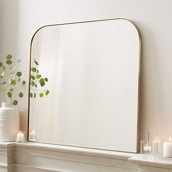 gold brass arched wall mirror leaning against white wall on fireplace mantel next to votive candles and a white vase with dried florals