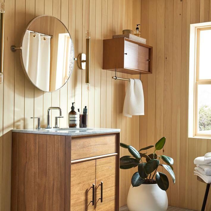 round brass pivot mirror on wood panel bathroom wall above vanity