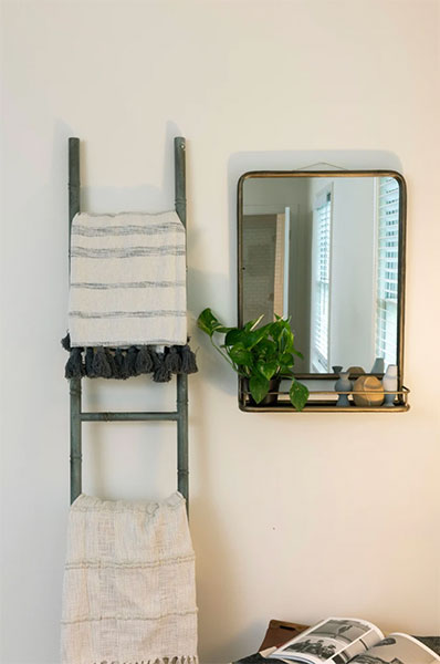 brass farmhouse wall mirror with shelf hanging on white wall next to ladder