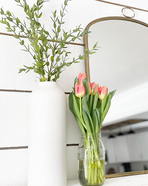 brass arched mirror on top of dresser in front of white shiplap wall next to white vase with flowers