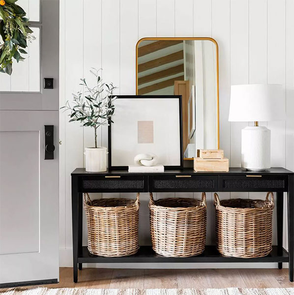brass gold rectangular mirror leaning against wall on top of black console table with lamp and 3 rattan baskets