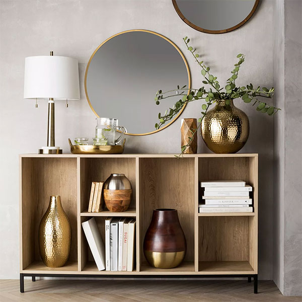 gold brass round mirror on beige wall above console table with lamp