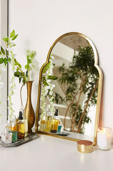 gold brass arched mirror leaning against white wall on top of dresser next to vases with dry florals