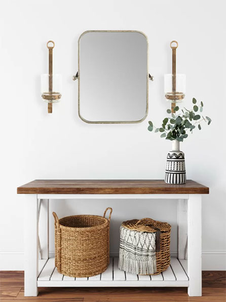 brass gold accent mirror hanging on white wall above wooden console table with baskets underneath