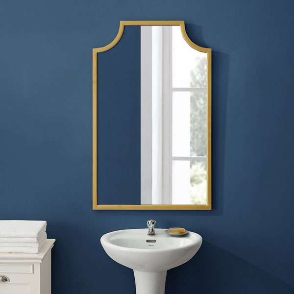 gold brass arched mirror on navy blue wall above pedestal sink