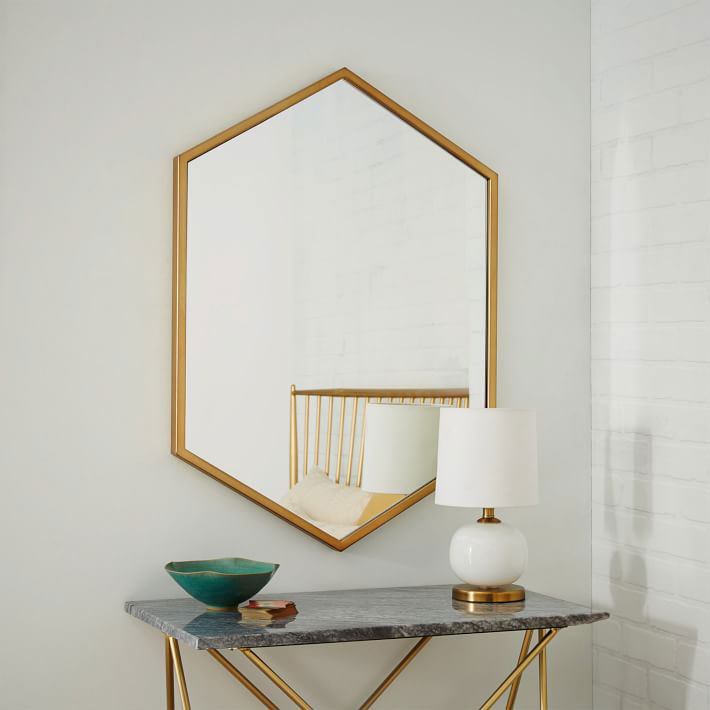 gold brass hexagon mirror on white wall above glass console table with small lamp